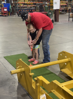 weiler employee helps his child play mini golf